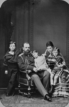 Photograph of Tsesarevich Alexander (1845-94), later Alexander III, and Tsesarevna Maria Feodorovna (1847-1928), later Empress of Russia, with their three eldest children Grand Duke Nicholas Alexandrovich (1868-1918), later Nicholas II, Grand Duke George Alexandrovich (1871-99) and Grand Duchess Xenia Alexandrovna (1875-1960). Tsesarevich Alexander is sitting in a chair at the centre of the group, wearing military uniform and with Grand Duchess Xenia sitting on his knee. Tsesarevna Maria…