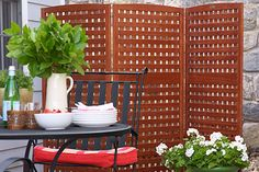 Use folding wood panels to build a privacy screen that will dress up your landscape and block out its less appealing aspects