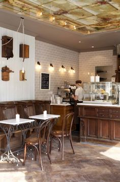 Soft gray subway tile with rich dark wood and white countertops. United Bakeries | Oslo, Norway