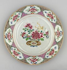 A Chinese famille rose porcelain plate painted at the centre w a peony & camellia posy in a squat urn. Rim of 8 shaped blossom reserves, outlined in green, upon an inner ground of pink diaper pattern & outer brown spiral ground.