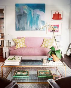 rug, clear coffee table w/ storage underneath, art prints for splash of colour