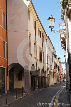Photo taken in via Altinate leads to the center of Padua in the Veneto (Italy). In the image you can see the facades of some historic buildings, particularly those located to the left of the image you see the arches that surround the arcades that are a hallmark of the city, of those on the right are noticed only a balcony and a series streetlights.