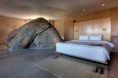 When building this home, Gracia studio worked around a large boulder. The rock now serves as a partition between bed and bath.
