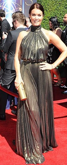 Bellamy Young hit the red carpet in a high-necked metallic gown with a cinched waist and pleating by Naeem Khan at the 2014 Creative Arts Emmys.