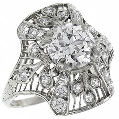 This is a gorgeous platinum diamond ring from the Art Deco era. The ring is centered with a sparkling GIA certified round old European cut diamond that weighs 1.50ct. The color of the diamond is J with VVS2 clarity. The center diamond is accentuated by smaller old mine cut and French cut diamonds that weigh approximately 1.00ct.
