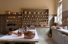 hanging skillets and smaller pots   Working over white linen in the kitchen at Attingham Park, UK, an 18th-century mansion with Regency interiors and deer park maintained by the National Trust
