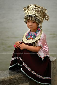 A lovely young girl in traditional costume and headdress at Guilin - China