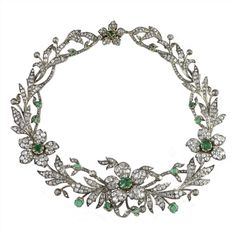 A magnificent Victorian emerald and diamond necklace, previously owned by the Habsburg imperial family of Austria, circa 1850,  comprising four flowers, each set with square-cut emerald to the centre of a cluster surround of old brilliant-cut and rose-cut diamond-set leaves, the diamonds estimated to weigh a total of 40 carats, all set in silver to a gold mount (maybe convertible??)