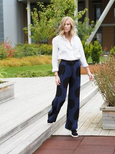 A button-down shirt is paired with wide-leg polka dot trousers and Puma sneakers