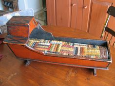 Antique cradle with old quilt. I've never seen this design before...the hooded canopy is unique.