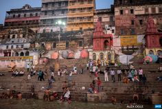 INDIA, Varanasi : People gather on the banks of the River Ganges as  Hindu devotees (bottom) perform a morning puja, or prayer ritual, on the  waterfront at Varanasi on September 18, 2015. The river is considered  holy in Hindu-majority India and millions of people visit it each year  to bathe in its water. AFP PHOTO / ALEX OGLE