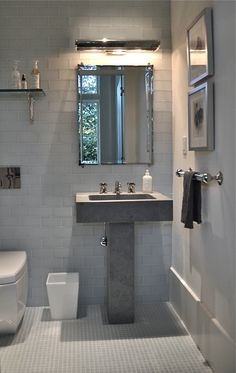 This bathroom has Anne Sacks pedestal stone sink and glass wall and floor tile. Urban Archeology mirror, glass shelf and towel bars/ hardware.