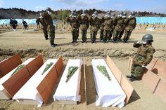 身元不明の遺体を埋葬する自衛隊員。ひつぎを納めるたびに敬礼をしていた=3日午後1時23分、宮城県東松島市