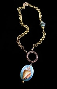 """""""Shore Thing, Sally Sea Shell""""    Do you love the beach and the shore?  Than this one is for you!  Russian hand painted glass with Bronze chain, Copper circle and Copper easy to use toggle.  One lone Clay bead off to the right.  Vermeil accents and hand wire wrapping with Swarovski Crystals.  Bronze is in.  Wear this with Khaki shorts and some flip flops while you relish the summer months.  19 inches in length and matching earrings sold separately.  $148.00       www.spitfire-designs.com"""