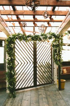 Modern gate + green and white floral garland + hanging globe lights | Image by Jenna Bechtolt Photography