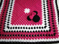 """Wouldnt this be adorable in your stroller at Disney?  This blanket features Minnie Mouse. Cute Minnie Mouse face with her signature bow on the front side. Classic Minnie Mouse colors in Bright Pink, black and white. The blanket is made in a large granny square crochet stitch. There is a Minnie Mouse face on the back side of the blanket. The back side of t he blanket does not have a bow. The Minnie Mouse blanket measures 31"""" wide x 31 long (78cm x 78 cm).  I also sell the pattern for this…"""
