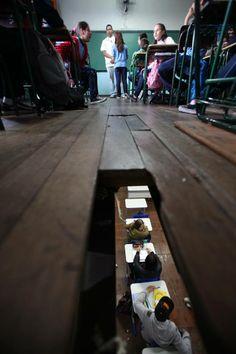 ©Allan Douglas Costa Pinto, publicada no Jornal Tribuna do Paraná, em uma reportagem que abordava o sucateamento do ensino no Paraná. A imagem, de 2012, mostra o buraco na sala de aula da Escola Estadual República Oriental do Uruguai. Recebeu menção honrosa no Prêmio Vladimir Herzog em 2013.