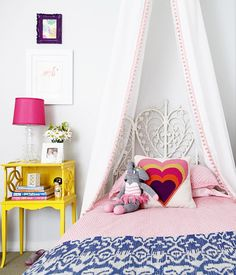 Small Shop Studio - Chic girl's room features DIY girl's bed canopy composed of Ikea Vivan Curtains trimmed with pink pom pom trim paired with white peacock headboard. Vintage white headboard with JR by John Robshaw Heath Pink Bedding and Etsy Ikat Bed Cover in Blue Twin Size as well as vintage refurbished yellow nightstand with Target acrylic lamp with hot pink lamps hade.