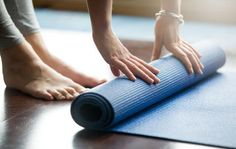 hands rolling up yoga mat