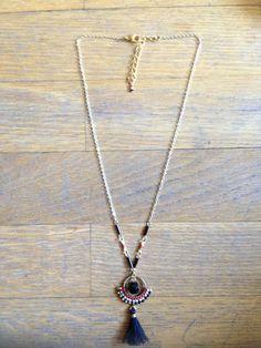 collier en perles du japon Miyuki doré / rouge / blanc / noir. tissage pelote sur rond metal doré 1,5cm de diamètre. pompon en coton noir. perle en verre noire. chaine en métal doré. longueur totale environ 42cm + 5cm chaine de réglage. modèle déposé fait à la main à paris.