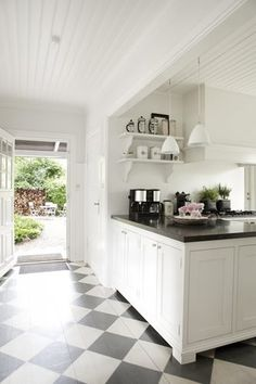 Checkered floor, black & white kitchen and close to outdoors.