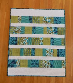 Cute strip quilt idea for wider quilts (like queen sized) - piece together multiple prints into wide rows and piece solid color rows in between.
