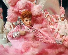 Ziegfeld Follies (1945) - Lucille Ball in the number Heres to the Ladies wearing a baby pink embellished lace dress with draped skirt long sleeves and bold shoulders paired to a feathered cape and matching headpiece.  The costumes were designed by Irene Maud Lentz.