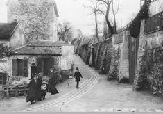"""On se promène devant le cabaret """"Au Lapin Agile"""", au coin de la rue Saint-Vincent et de la rue des Saules, vers 1900  (Paris 18ème)."""
