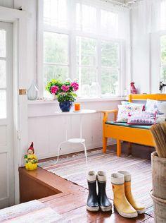 """Timo-vävy kunnosti etukuistin ja kaivoi esille upeat lattialankut muovimaton alta. Kuistilla on kaksi pirteää oranssia sohvaa, jotka ostettiin tuttavan navetan vintiltä. Veikeä pihatonttu on kirpputorilta ja sohvan takana olevan pinkin """"pingviinin"""" Hanna-tytär on tehnyt kuvataidelukiossa. Muut esineet ovat kirpputorilta."""