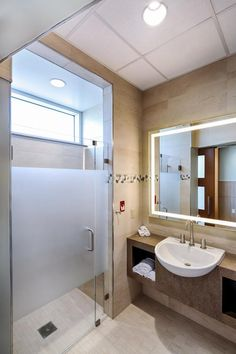 Patient bathrooms at WakeMed North, which opened in May, were designed with a hotel experience in mind and are rendered in soft tones and natural materials, including river rock accents, porcelain tile floors, quartz vanities, and back-lit LED mirrors. Showers have glass doors with a transom window to the exterior that brings natural light to the entire space. Credit: Tzu Chen Photography.