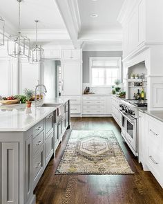 Elegant kitchen design with white shaker cabinets and a gray center island features a yellow and gray vintage rug layered on dark stained wood floors.