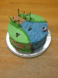"8"" double layer fishing theme. Toothpick cat tails, royal icing cattail leaves, chocolate rocks, plastic fishing bob. Buttercream icing for the rest"