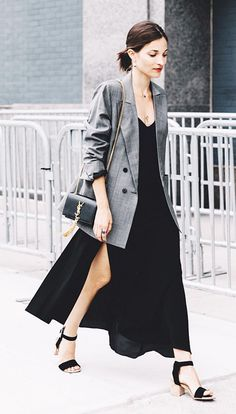 A black slip dress is paired with a gray blazer, Saint Laurent bag, and sandals