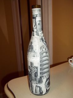 Decoupaged wine bottle with pictures from around the world. Currently being used to hold incense.