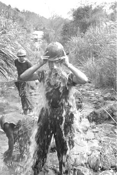 A US Marine of the 1st Marine Regiment cools off by dumping a helmet-full of water on his head, 1968.