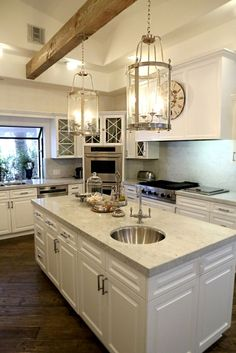 Tour Kyle Richards' Home (and Closet!) Kyle Richards kitchen @ Home Design Ideas.Love the single wood beam with the beautiful lights hanging down.sweeps your eyes upward in an otherwise all-white kitchen. Home Design, Home Interior Design, Design Ideas, New Kitchen, Kitchen Decor, Kitchen Design, Kitchen Island, Kitchen Wood, Awesome Kitchen