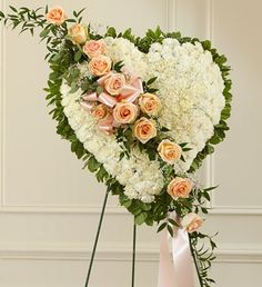 Solid heart standing spray, accented with a slash of peach roses. Symbol of love, sympathy, & support