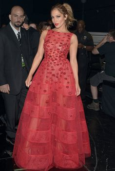 Jennifer Lopez in a sheer, floor-length red gown with a matching lip backstage at the awards