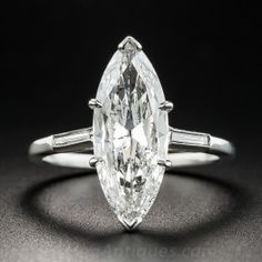 This aerodynamic dazzler, weighing 2.40 carats, dating from the mid-20th-century, radiates with just shy of 3/4 inch of intense sparkle! The sleekly streamlined stone is elegantly presented in a hand fabricated platinum mounting set low between a pair of slender straight baguette diamonds. A singular, stunning, classic and impressive finger-hugger (they don't make 'em like this anymore). Accompanied by a GIA Diamond Grading Report stating: G color - SI2 clarity. Currently ring size 6.