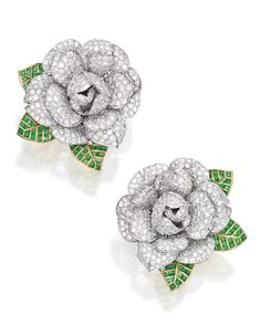 PAIR OF TWO-COLOR GOLD, DIAMOND AND EMERALD EARCLIPS. Designed as gardenias pavé-set with round diamonds weighing approximately 15.50 carats, with leaves accented by calibré-cut emeralds weighing approximately 6.75 carats.