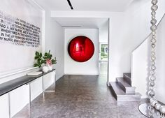 A deep-red Anish Kapoor sculpture greets visitors in the entrance hall of a Neuilly-sur- Seine, France, house designed by Charles Zana for a couple with a blue-chip contemporary-art collection. The text painting is by Richard Prince, and the console is by Eric Schmitt; a dramatic glass- bead sculpture by Jean-Michel Othoniel dangles from 30 feet above.