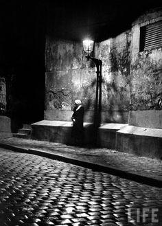 Alfred Eisenstaedt: Woman under streetlight in Montmartre at night. Paris, France, 1963