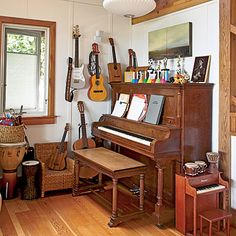 Jack Johnson's music nook:  child's piano & mini hand drums beside upright piano, wall hung guitars and plenty of hand drums.  Awesome.