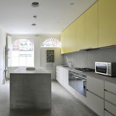 Love the bold yellow kitchen cupboards paired with concrete bench tops