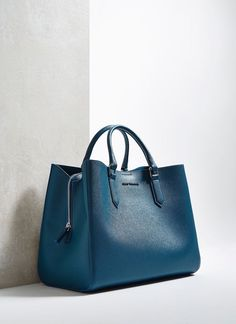 Vegan leather tote bag featuring three distinct compartments. The middle section fastens with a zipper and could fit a tablet computer. The other two close with a magnetic clasp and the bag comes with a matching, removable, and adjustable shoulder strap.