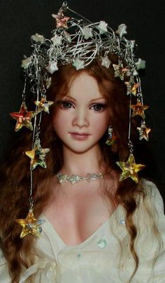 """""""Nevaeh: Goddess of Heaven and Earth"""" by Lorella Falconi. OOAK, 32″, Porcelain & soft body with armature which allows the doll to pose. Slate blue painted eyes. Handmade angora wig. Silver crown with mother of pearl stars & Swarovski Crystals. Doll represents Heaven & Earth - The upper half represents Heaven (stars in crown), & the lower half represents earth by the vintage silk flowers that embellish her silk gown in white, green (earth) & blue (waters). She carries a strand of pearls…"""