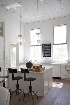 love the high ceilings and pendant lamps in this bright and beachy kitchen