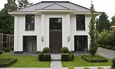 Eine große, weiße Villa mit dunklen eye catchern wie der Tür und den Fensterrahmen. Die Villa sieht dadurch sehr hochwertig aus und bietet viel Platz!