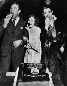 Randolph Scott, Nancy Carroll, and Cary Grant dig into birthday cake in 1933. Scott was born Jan. 23, 1898, and Grant was born Jan. 18, 1904.