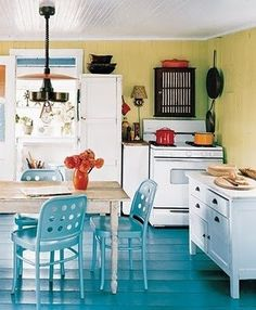 pale yellow walls, turquoise blue floors, white cabinets, and dark colored accents